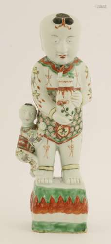 A Chinese porcelain famille verte figure, 17th century, of a boy holding a vase with another boy ...