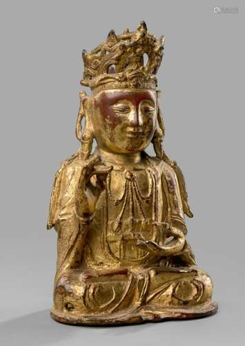 A GILT- AND RED-LACQUERED BRONZE FIGURE OF GUANYIN, CHINA, 17th ct., seated in vajrasana with the right hand holding willow-twig and the left supporting a vase, wearing various garments, bejewelled, his face displaying a serene expression and the hair combed in a chignon secured with a tiara - Property from an old German Noble collection, assembled in the 1960s and 70s - Wear
