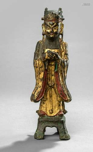 A GILT- AND RED-LACQUERED BRONZE FIGURE OF AN IMMORTAL, CHINA, 17th ct., standing on a pedestal on four legs, his hands clasped in front of his breast, wearing various garments, his face displaying a stern expression with raised eyebrows, long beard and moustache framing his mouth and his head topped with a cap - Property from an old Dutch private collection, assembled from 1950 till the 1990s, by descent to the present owner - Wear, sceptre lost