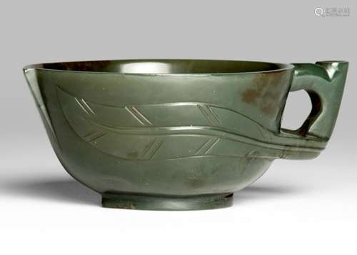 A DARK GREEN JADE PEACH-SHAPED CUP, China, Qing Dynasty. The handle transitioning into peach leaves which in turn extend across the cup's outer walls - Property from an important German private collection, acquired at Kunsthandel Heinz Reichert, Freiburg, 31 Feb 1979 - Very minor wear