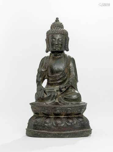 A BRONZE FIGURE OF BUDDHA SHAKYAMUNI, CHINA, 16th ct., seated in vajrasana on a lotus base with his right hand in bhumisparshamudra and the left resting on his lap, wearing a monastic garment, his face displaying a serene expression with downcast eyes, the curled hair and ushnisha topped with a lotus-bud - Property from an old Bavarian private collection, assembled by the father of the present owner till the 1980'ies - Base with very small losses and few dents