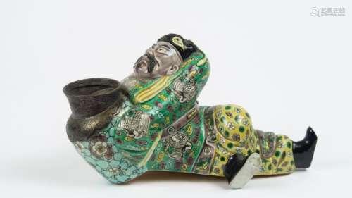 Sujet en biscuit émaillé polychrome aux émaux de la famille verte, figurant un Li Bai allongé tenant une jarre à vin métallique dans les mains. <br/>Chine, dynastie Qing, XIX ème siècle. <br/>L. 19 cm <br/>(Accidents)