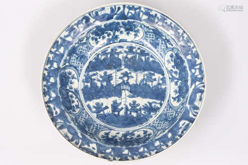 Chine, XVI° siècle. Grand plat en porcelaine Swatow à décor bleu et blanc de pagodes et de fleurs. La base non glacurée. Diam. 42cm. (Accroc sur le col).