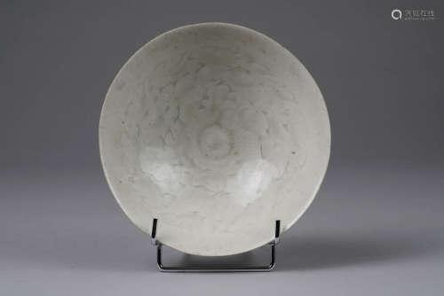Chine, époque Song. Coupe en porcelaine à couverte dite Qingbai à décor incisé de nuages. La base blanchâtre non glaçurée annotée d'un caractère chinois anciennement peint. Diam. 17.5cm.