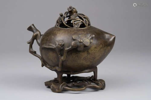 Chine, dynastie Qing, XVII°siècle. Brûle parfum à patine brune et forme de pêche de longévité. Couvercle ajouré et socle assortis. H 18.5cm.