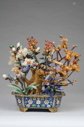 Chine, XX° siècle. Bonzaï en pierre dure dans une jardinière en émail cloisonné. Jolie utilisation de jadéite, agate et lapis lazuli. H 22cm. Bon état.