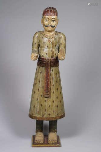 Inde, fin XIX° siècle. Grand personnage debout en bois sculpté anciennement en paire et probablement tenant un gong. Restes de polychromie et de vêtements décorés de roses. H 97cm.