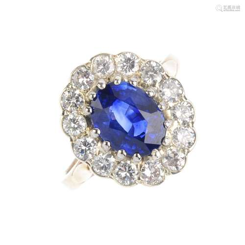 A 9ct gold sapphire and diamond cluster ring. The oval-shape sapphire, with brilliant-cut diamond