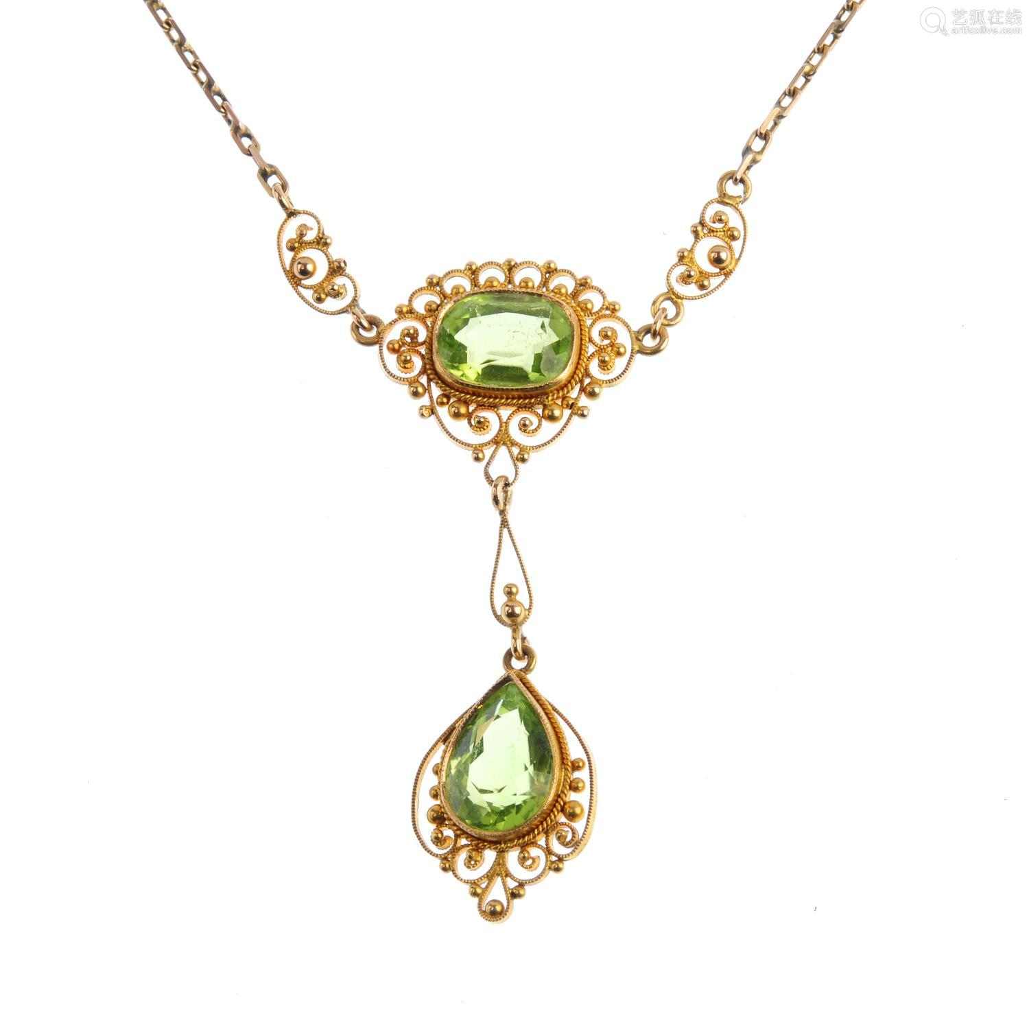 An early 20th century gold peridot necklace. The pear-shape peridot suspended from a cushion-shape