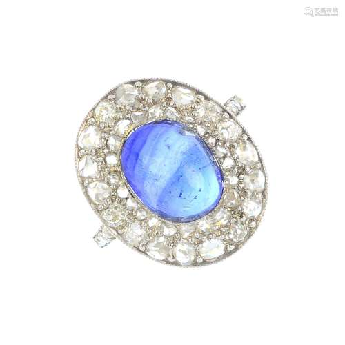 A Ceylon sapphire and diamond cluster ring. The oval sapphire cabochon, weighing 5.94cts, with