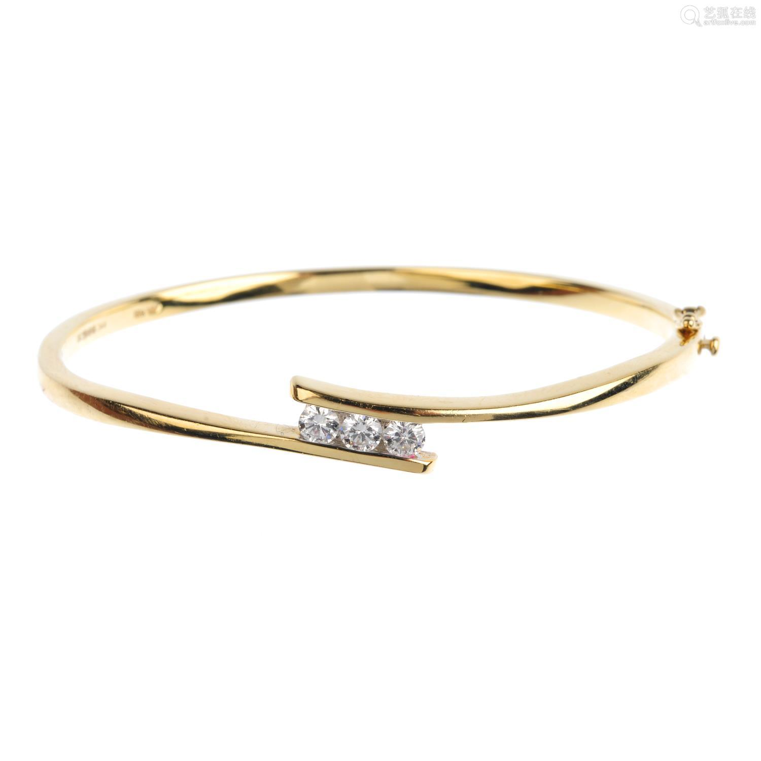 An 18ct gold diamond hinged bangle. The brilliant-cut diamond line, with crossover sides.