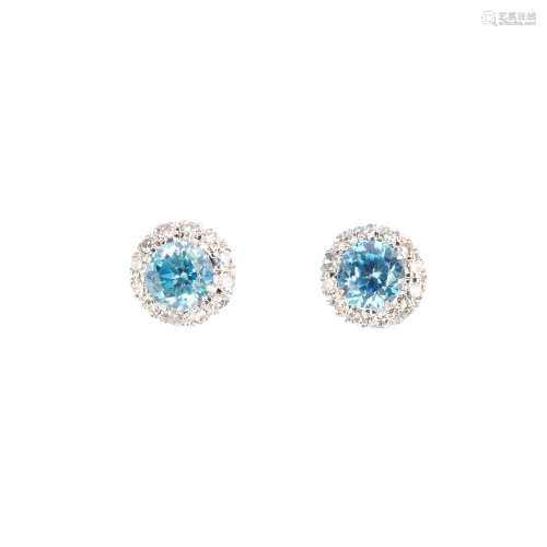 A pair of zircon and diamond earrings. Each designed as a circular-shape blue zircon, with single-