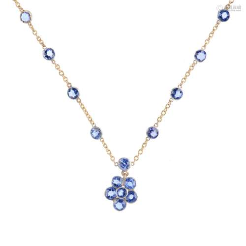 A sapphire necklace. Of bi-colour design, the circular-shape sapphire floral cluster, suspended from