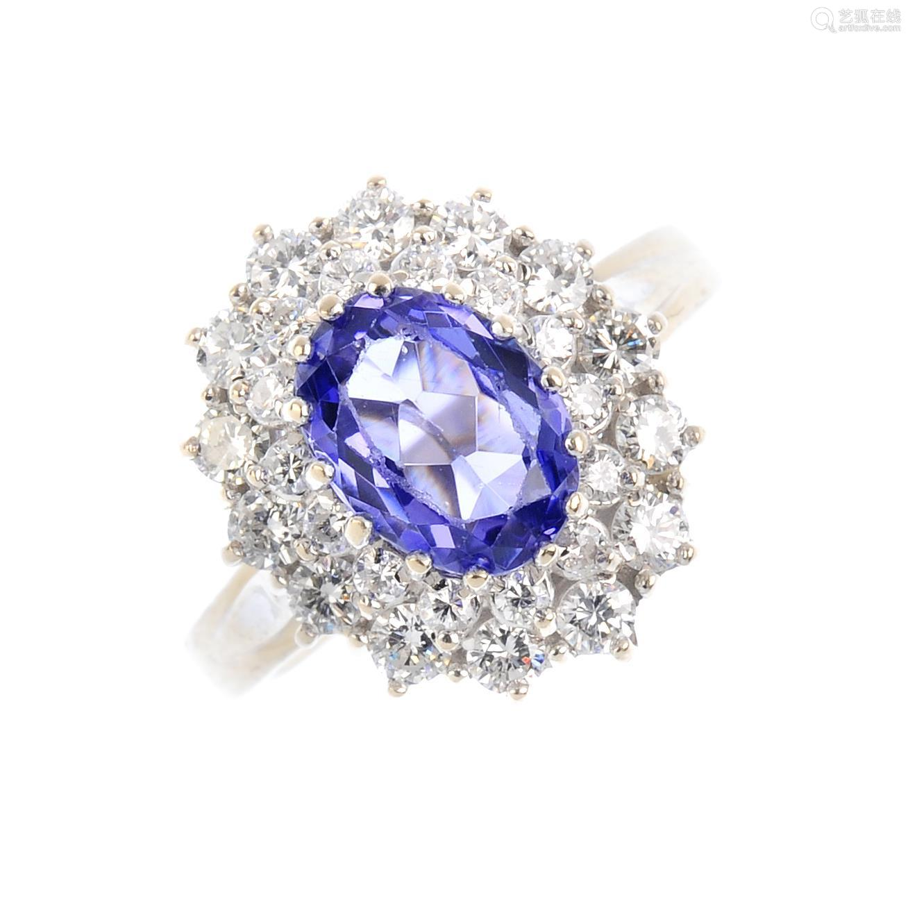An 18ct gold tanzanite and diamond cluster ring. The oval-shape tanzanite, with brilliant-cut