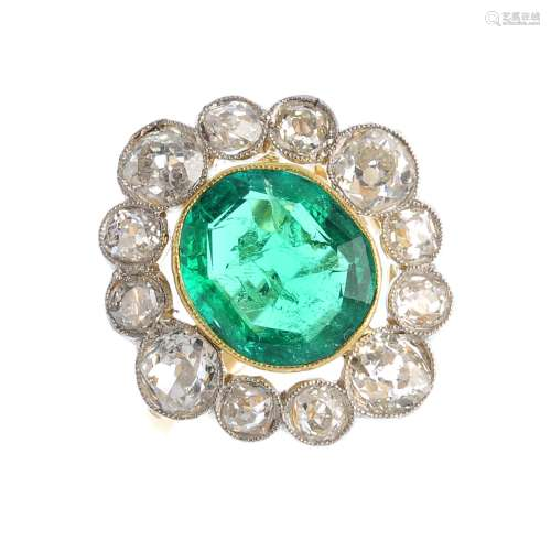 A Colombian emerald and diamond cluster ring. The oval-shape emerald, with old-cut diamond surround.