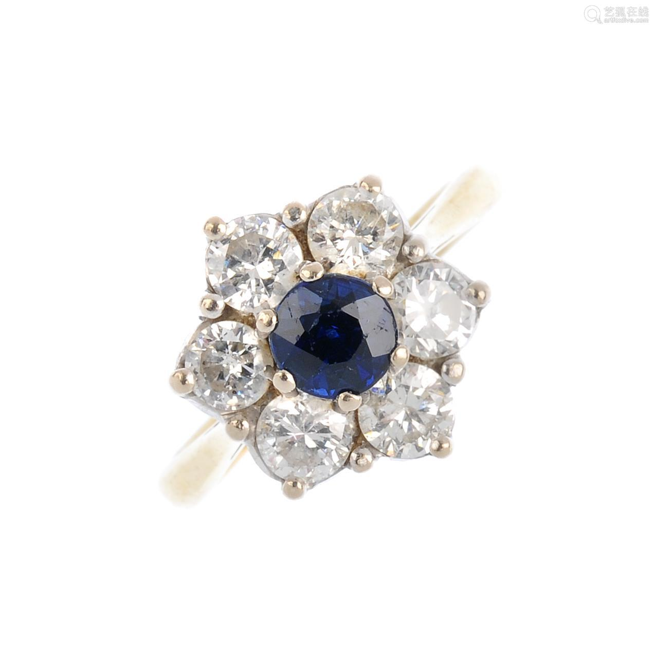 An 18ct gold sapphire and diamond cluster ring. The circular-shape sapphire, with brilliant-cut