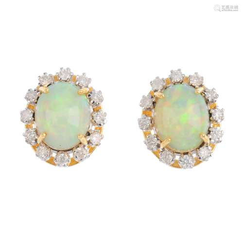 A pair of 18ct gold opal and diamond cluster earrings. Each designed as an oval opal cabochon,