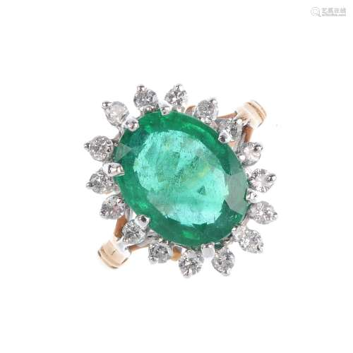 An emerald and diamond cluster ring. The oval-shape emerald, with brilliant-cut diamond surround and