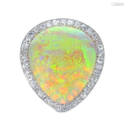An opal and diamond clip. The pear-shape opal cabochon,