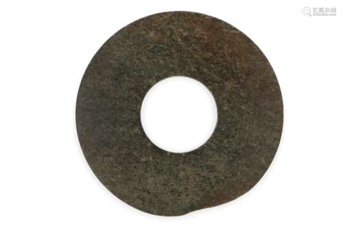 An archaïc large green jade bi-disc. The plain formed green jade with white spots. Part of the rim in irregular circle line. No ornaments. China, possibly Neolithic or early Zhou, ca. 2000 - 1000 B.C. Diam. 18,5 cm.