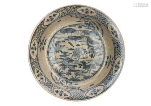 A blue and white ceramic charger with craquelé decor of two deer in a landscape. Unmarked. China, Ming. Diam. 39,5 cm.