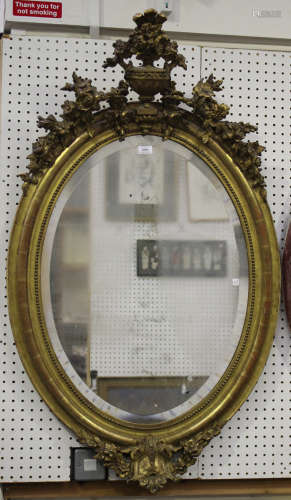 A mid-Victorian giltwood and gesso framed oval wall mirror with urn surmount