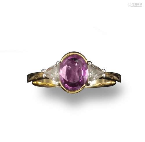 A pink sapphire and diamond ring, the oval-shaped sapphire set with two triangular shoulder diamonds