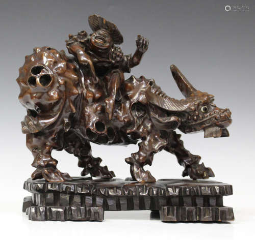 A Chinese carved gnarled hardwood figure group of a boy seated on the back of a water buffalo, early