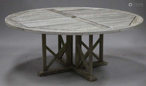 A large late 20th century teak slatted garden table, the circular top above 'X' framed supports,