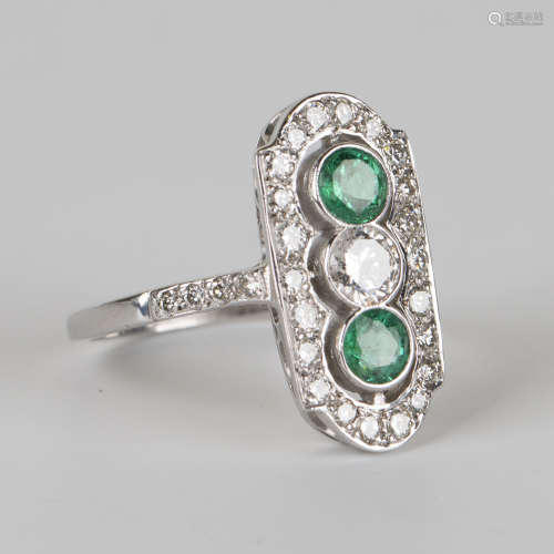 An 18ct white gold, emerald and diamond panel shaped ring, collet set with the principal circular