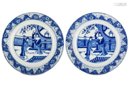 A PAIR OF CHINESE BLUE AND WHITE 'LADIES' DISHES. Kangxi. Each with a central roundel enclosing two ladies on a garden veranda below flowering prunus branches, within a border of prunus flower heads borne on swirling and frothing waves, six