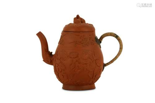 A CHINESE YIXING ZISHA TEAPOT AND COVER. Kangxi. The rounded body supported on a splayed foot, and surmounted by a domed cover with a finial formed as a well modelled squirrel, the body moulded with flowering plants below a band of floral spray, the