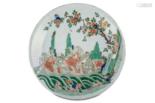 A CHINESE FAMILLE VERTE 'JUMPING CARP' CHARGER. Kangxi. Finely painted to the interior with three iron red carp among frothing waves, from which emerge jagged rocks, with a flowering plum tree extending overhead, with fallen flower heads tossed on