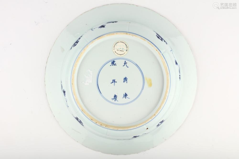 A CHINESE BLUE AND WHITE 'LADIES' BASIN DISH. Kangxi mark and of the period. The deep bowl with a central roundel enclosing ladies separated by a flowering plum tree on a stand, enclosed within a band of panels enclosing the repeated motif, six