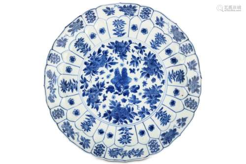 A CHINESE BLUE AND WHITE 'PEONIES' MOULDED DISH. Kangxi mark and of the period. Decorated with a central roundel enclosing floral bouquets, enclosed within a border of moulded lappets each enclosing a single flower, within a further band of