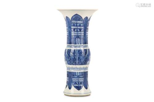 A SMALL CHINESE BLUE AND WHITE BEAKER VASE, GU. Kangxi. Decorated with archaistic taotie masks to the mid-section and lappets to the flaring base and neck, 36cm H, 17.5cm diameter. 清康熙   青花饕餮紋觚式瓶 For blue and white vases with
