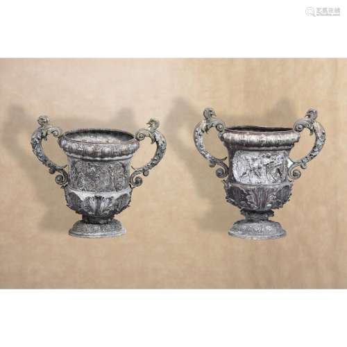 A pair of Victorian cast lead twin handled urns in Baroque style