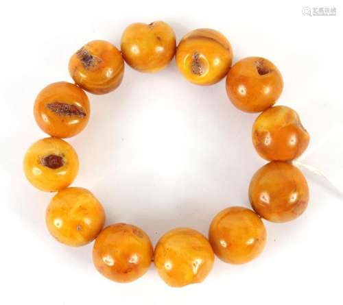 YELLOW BEESWAX BEAD BRACELET - Twelve large polished russet-yellow beads, each with an irregular dimple on the surface