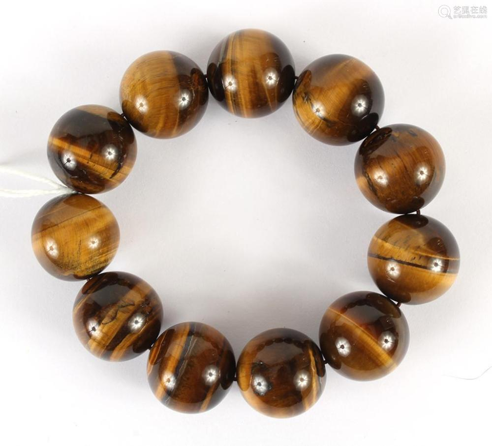 TIGER'S-EYE QUARTZ BEAD BRACELET - Eleven highly polished 2 cm round tiger's-eye hardstone beads are strung on a flexible cord bracel