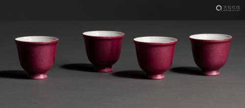 A SET OF FOUR PUCE-ENAMELLED PORCELAIN CUPS