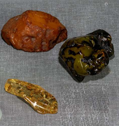 A GROUP OF THREE AMBER FOUNDLINGS