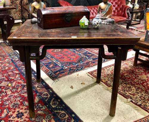 An antique Chinese elm table, the rectangular top raised on four turned legs, 99 cm x 76 cm x 83