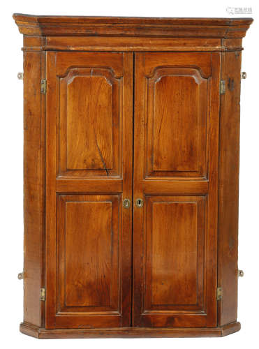 A mid-18th century elm and oak hanging corner cupboard, with a pair of fielded panel doors enclosing