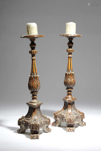A pair of 19th century continental painted wood altar candlesticks, with fluted and leaf carved