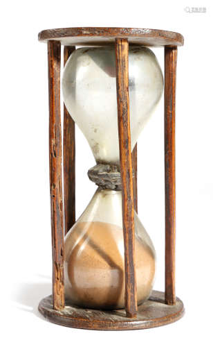 An early 18th century ash sandglass, with four stick supports, the double hourglass bulbs