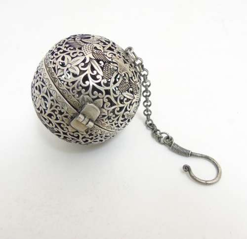 A Chinese white metal censor ball with pierced decoration of birds etc 2 1/4