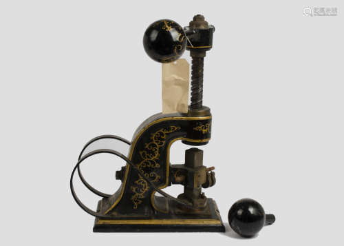 A late 19th/early 20th Century painted metal stamping machine, gilt scroll decoration on black