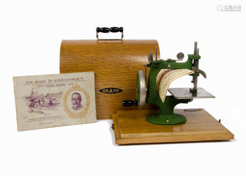 A wooden cased child's Grain manual sewing machine, green cast iron G frame on wooden base. Together