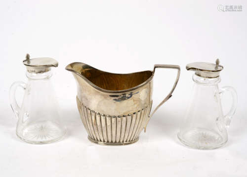 A Victorian silver milk jug, hallmarked Sheffield 1899, designed by the Atkin brothers, with