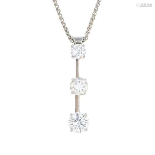 A diamond three-stone pendant. The graduated